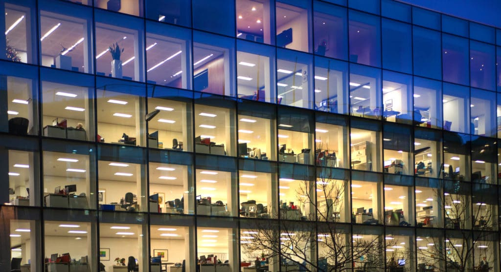 Office Building mit grosser Glassfront bei Nacht. UGR Blendung